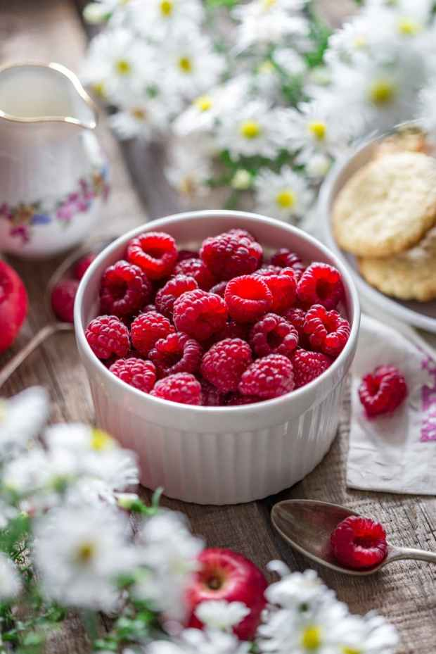 close up of raspberries in bowl on table